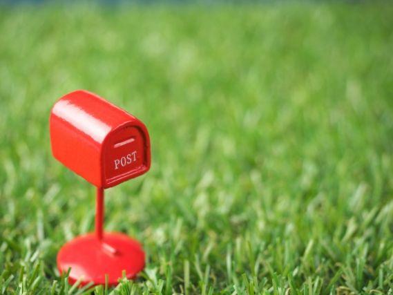 芝生に置かれた赤いポスト